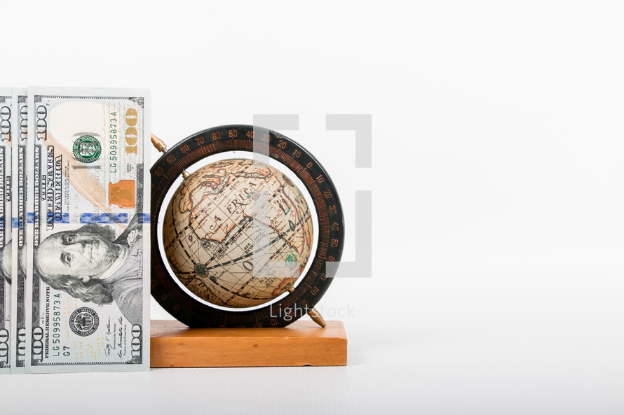 one hundred dollar bills and globe