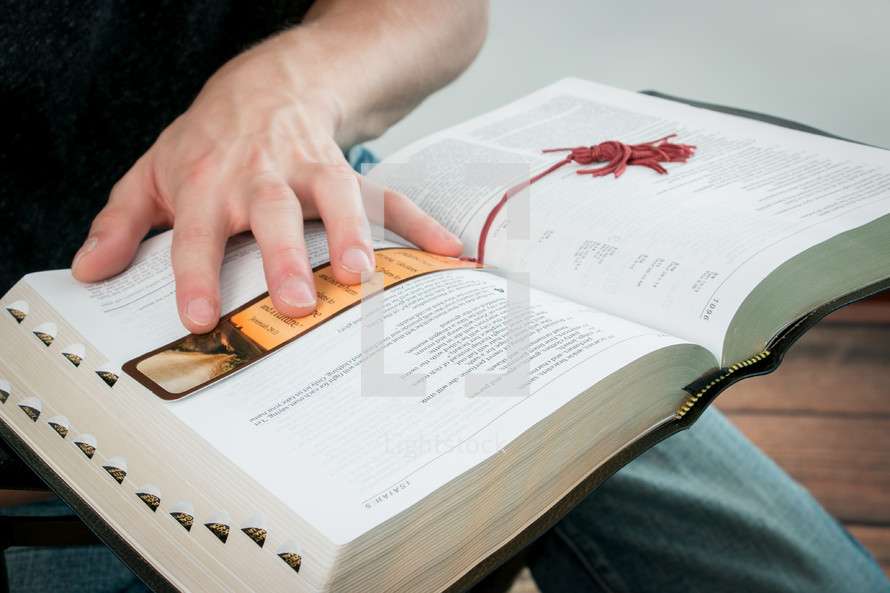 man's hand on a Bible