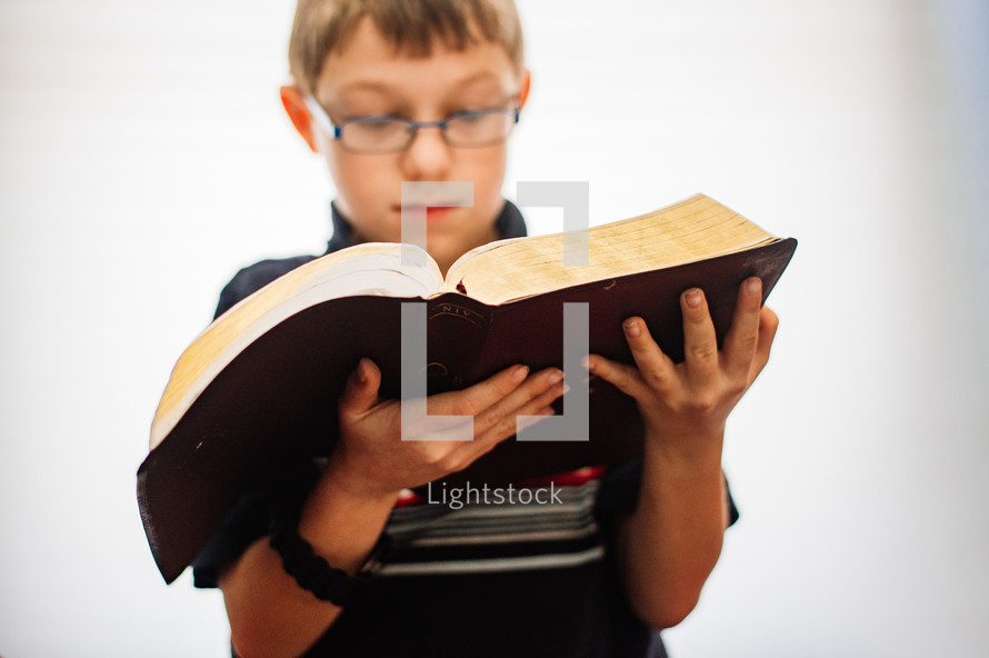 A 11 year old boy reading an open Bible  with a white background