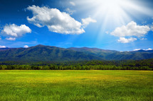 sunlight on a mountain behind an open grassy field