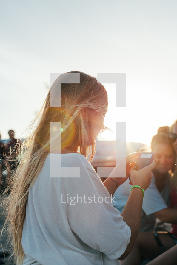 teen girl on a beach taking a picture of her friends with her cellphone