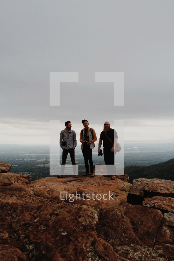 friends standing together at the top of a mountain