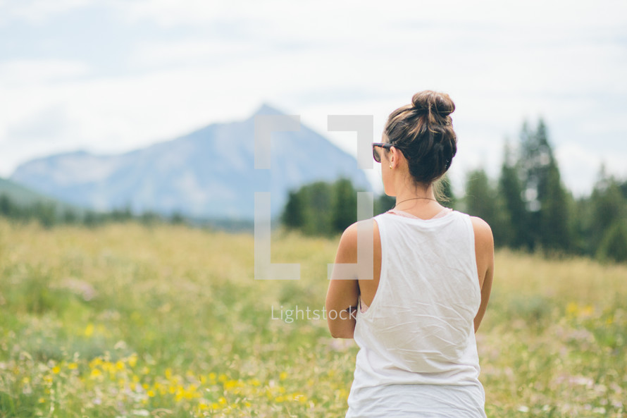 woman standing outdoors looking at a mountain peak