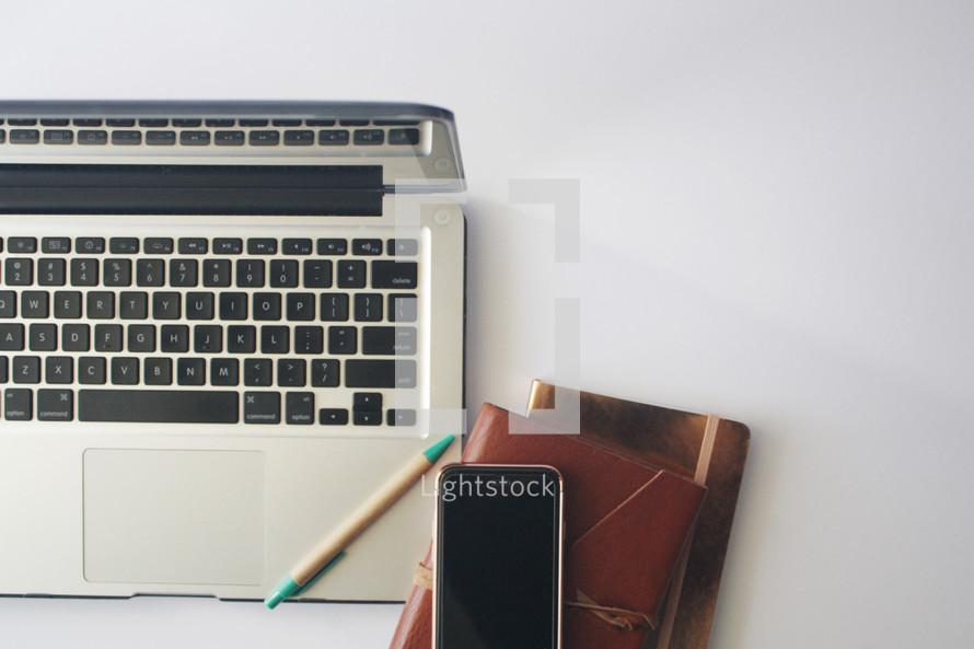 laptop computer, cellphone, journal, pencil
