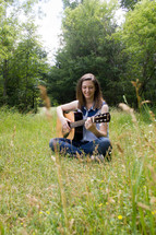 woman sitting in a field playing her guitar