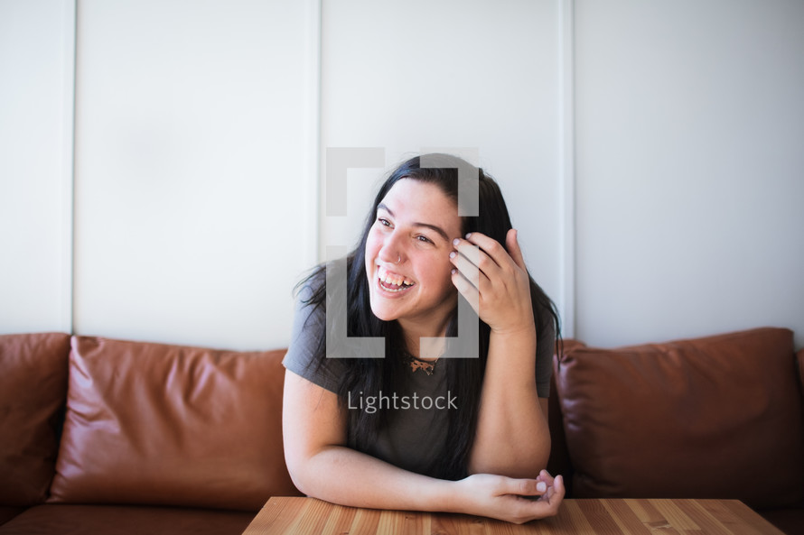 a smiling young woman sitting on a couch