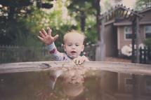 A baby boy plays in the water of a birdbath.