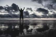 a man standing on a beach on wet sand with hands raised at sunset