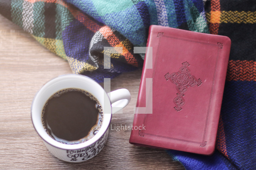 coffee cup and Bible on a plaid flannel blanket