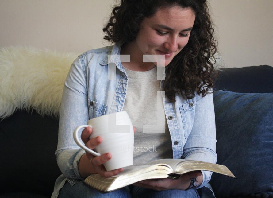 a woman holding a mug reading a Bible