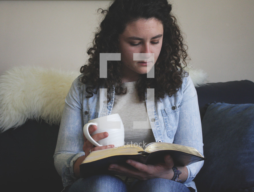a woman holding a mug reading a Bible