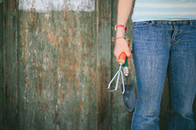 Teen holding a claw garden tool and spade shovel near a half painted fence.