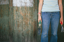 Woman holding garden tools, standing against an old wooden wall