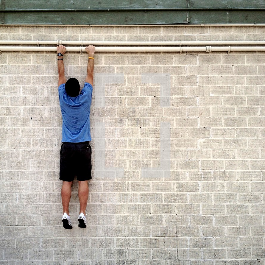 Man hanging on side of a brick wall