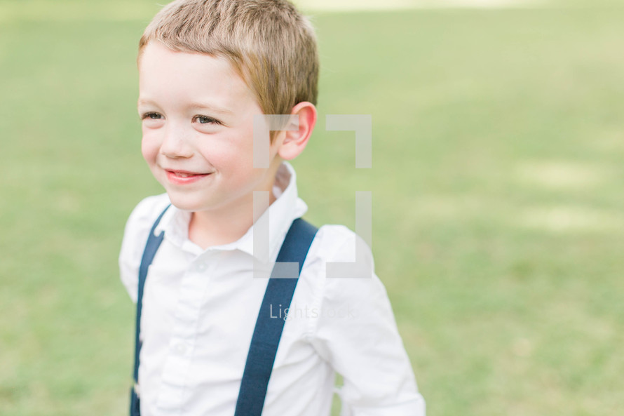 a smiling boy child in suspenders
