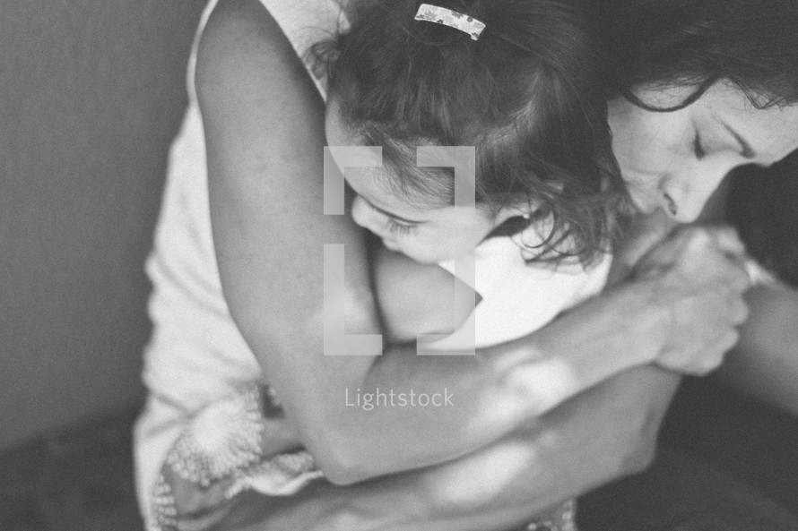 A mother hugging her daughter.