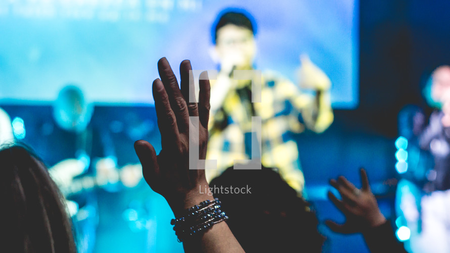 people singing on stage and audience with raised hands