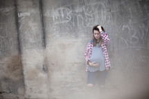A pregnant teenager stands against a wall covered in graffiti.