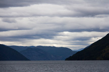 Landscape view of Sognefjord and the surrounding mountains in western Norway. Taken from the Flam to Bergen ferry under overcast skies taken at blue hour.