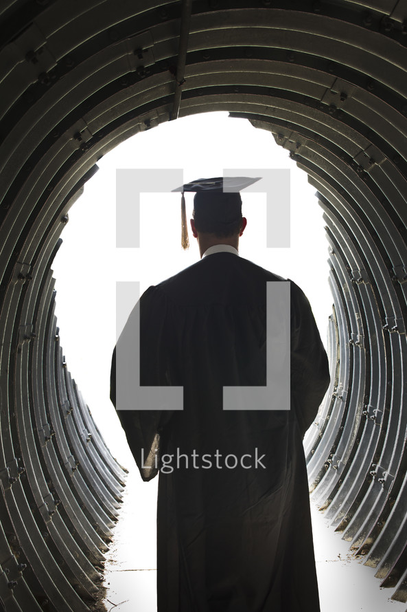 graduate walking through a tunnel