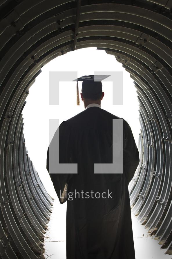 graduate walking through a tunnel