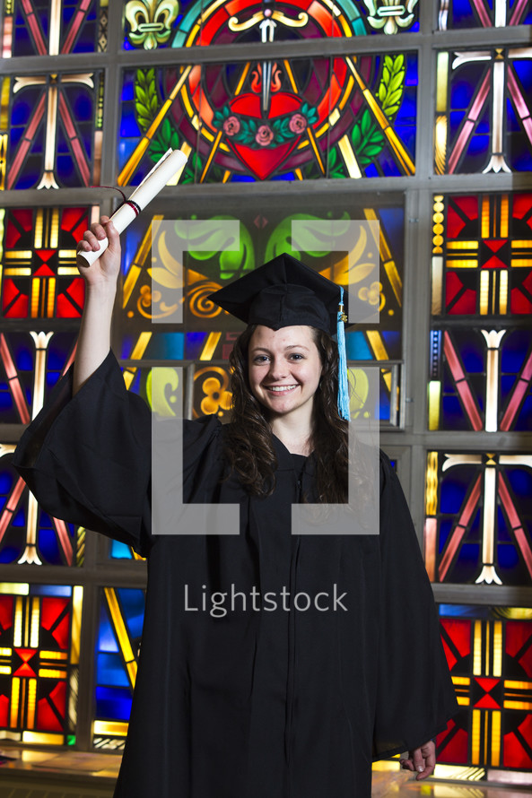 graduate holding up her diploma in front of a stained glass window