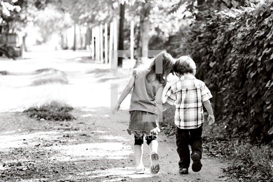 a boy and girl child walking down a path