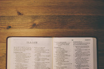 Open Bible on a wooden table.