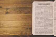 Bible on a wooden table open to the book of 2 Corinthians.