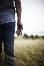 Young man standing in a field with Bible at his side