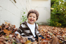 Toddler playing in Autumn leaves