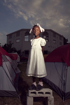 girl in dress standing next to tents