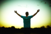A man, with hands raised, worshipping at sunrise