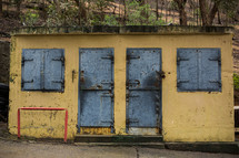 closed doors and shutters on a yellow shanty