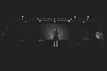 woman singing on stage at a contemporary worship service