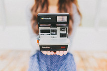 A young woman holds a Polaroid camera