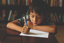 Boy drawing in a library