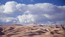 clouds in the sky over desert sand dunes