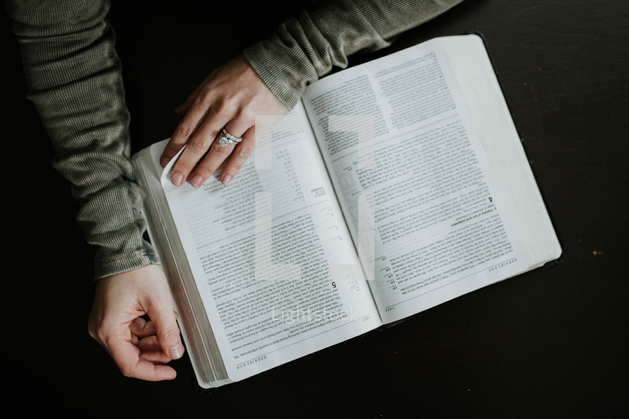 a woman reading a Bible on her lap