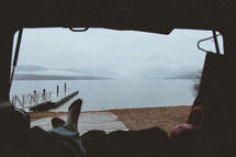 sitting in the back of an SUV looking out at a lake