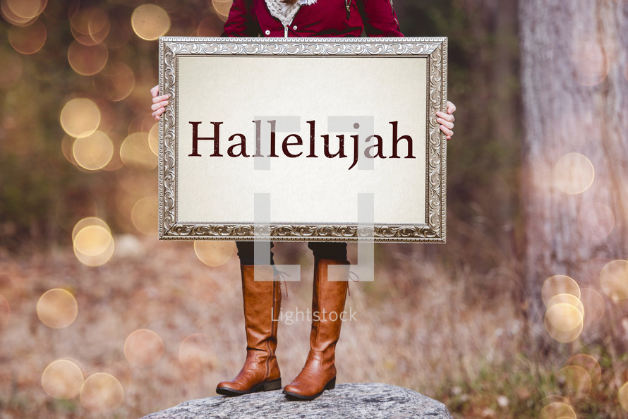 a woman holding a sign the reads hallelujah