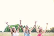 women standing in a field with raised held  hands