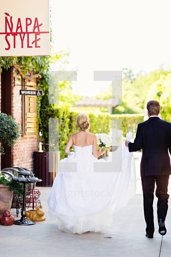 Groom holding bride's wedding train while walking Napa Style, wedding