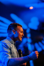 A man speaking intently into a microphone with fist clenched and eyes closed speaker praying prayer preaching teaching passion for Christ