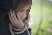 shrouded girl with hands tied