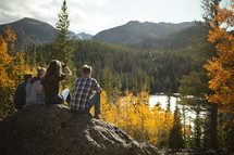 young adults sitting on a rock looking out at a lake in fall
