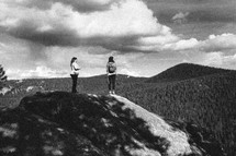 two women stand on top of a rock in the wilderness