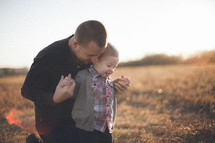 Man kneeling in grassy field behind toddler child, holding hands at dusk.