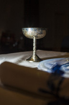 Silver chalice sitting on top of table with tablecloth.