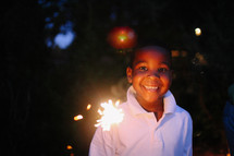 boy with a smile holding a sparkler